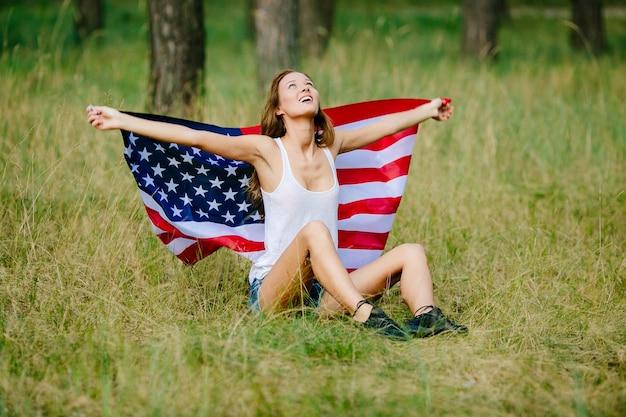 Glückliches mädchen sitzt auf dem gras mit der amerikanischen flagge