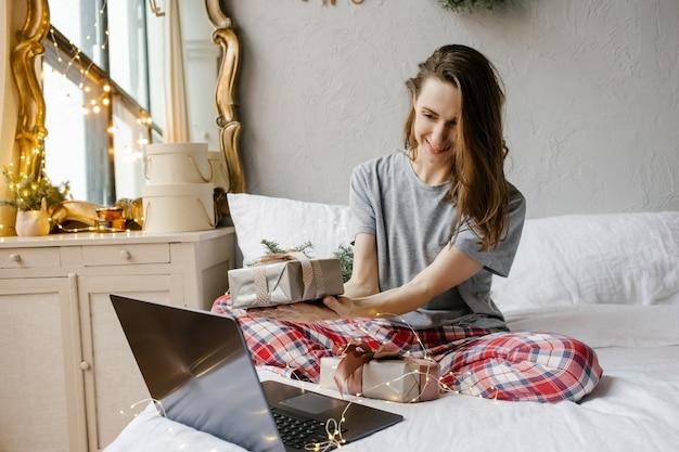 Glückliches mädchen sitzt vor einem computerbildschirm mit einer geschenkbox in ihren händen zu hause