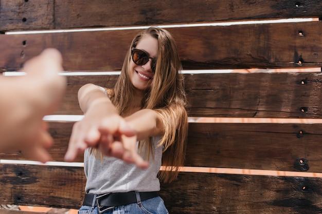 Glückliches mädchen trägt trendigen schwarzen gürtel, der positive emotionen ausdrückt. foto der begeisterten brünetten frau in der sonnenbrille, die auf holzwand tanzt.
