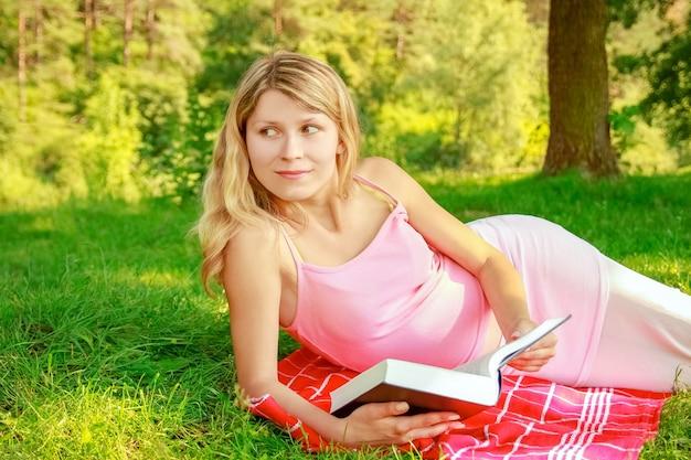 Glückliches mädchen über die natur des lesens eines buches im park