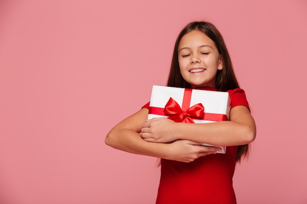 Glückliches mädchen umarmen ihr geschenk und lächeln lokalisiert