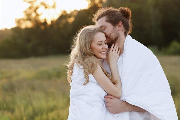 Glückliches mädchen und kerl in einer decke, die bei sonnenuntergang küsst.