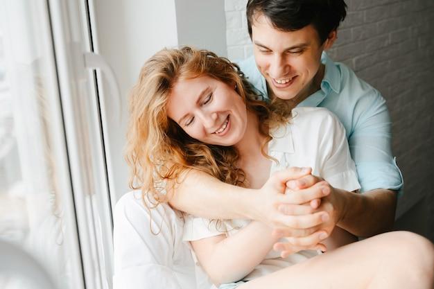 Glückliches mädchen und mann, die nahe fenster im haus umarmen. weiße und blaue kleidung. valentinstag.