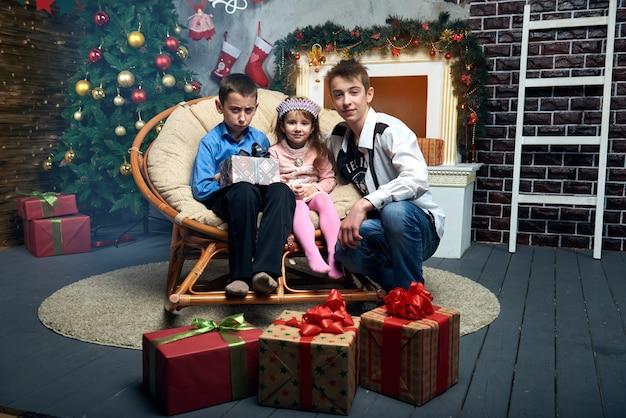 Glückliches mädchen und zwei jungen verbringen zeit zusammen in den winterferien zu hause am kamin nahe dem baum mit vielen geschenken. nettes kleines mädchen und zwei jungen im stuhl am weihnachtsbaum.