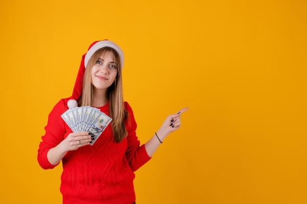 Glückliches mädchen, welches in der hand das geld zeigt finger auf das copyspace trägt sankt-hut hält