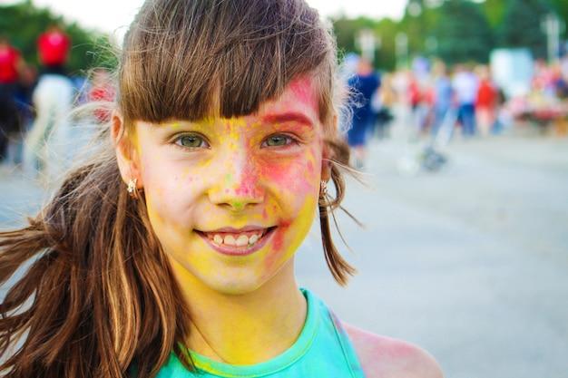 Glückliches mädchen zeigt klasse mit holi farbe.