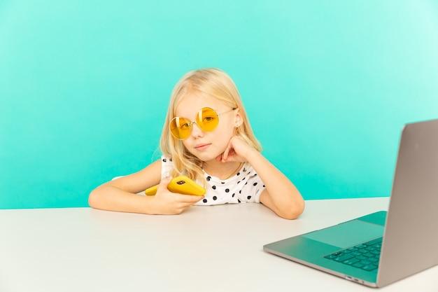 Glückliches mädchen zu hause, das vor kamera für vlog spricht. kind macht selbst foto und video als blogger arbeiten, video-tutorial für das internet aufnehmen.