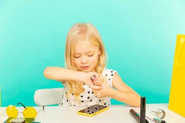 Glückliches mädchen zu hause, das vor kamera für vlog spricht. kleines kind, das als blogger arbeitet und video-tutorial für das internet aufzeichnet.