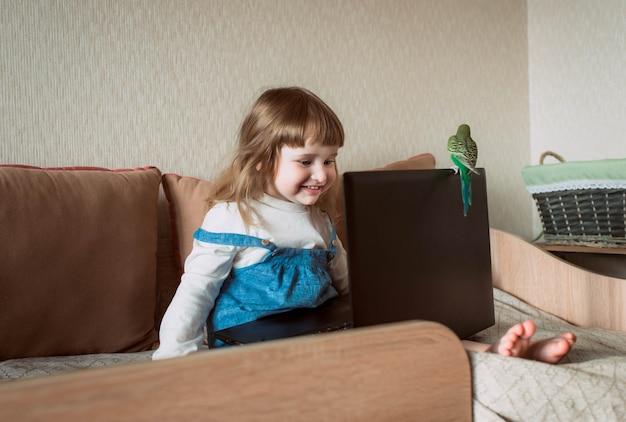 Glückliches mädchen zu hause. haustier zu hause. wellensittich. laptop und geräte. baby beobachten cartoons, online-spiele.