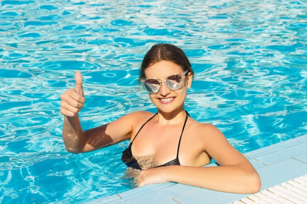 Glückliches mädchengesicht zeigt daumen oben im swimmingpool