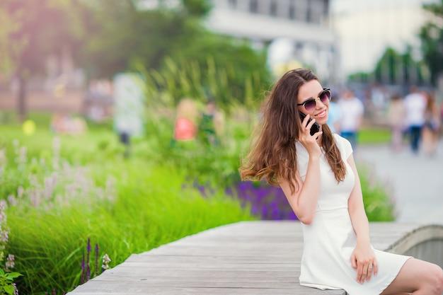 Glückliches mädchengespräch durch smartphone draußen im park. junge attraktive frau mit handy feiertagsreiseziel im tourismus draußen genießend und konzept erforschend