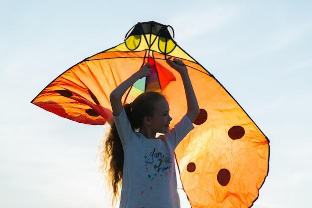 Glückliches mädchenspiel mit drachen auf dem feld zur sonnenuntergangzeit