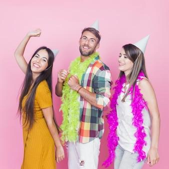 Glückliches männliches tanzen mit seinen zwei weiblichen freunden in der party