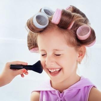 Glückliches malenkay-kind, das ihr make-up und frisur tut. quadrat. konzept des lebensstils, kindheit, kosmetik, spiel.