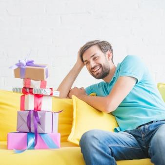 Glückliches mannschauen von gestapelten geburtstagsgeschenken