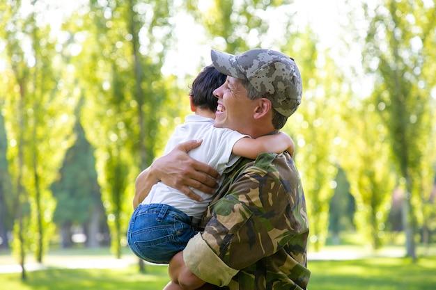 Glückliches militärisches vatertreffen mit kleinem sohn nach missionsreise, jungen in den armen haltend und lächelnd. familientreffen oder rückkehr nach hause konzept
