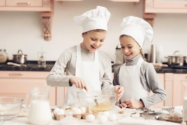 Glückliches mischendes ei des jungen und des mädchens, das an der küche kocht.