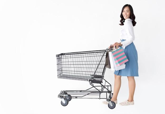 Glückliches modisches asiatisches mädchen mit einkaufstasche auf weißer isolierwand im roten thema