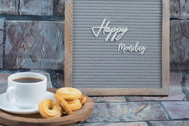 Glückliches montagplakat mit einer tasse getränk und keksen herum