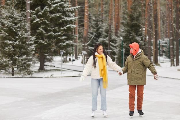 Glückliches multiethnisches paar, das auf eisbahn im winterwald während der winterferien skatet