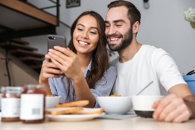 Glückliches multiethnisches paar, das frühstück in der küche hat und handy ansieht