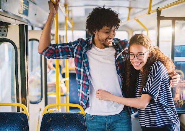 Glückliches multikulturelles junges paar, das für eine bar in einem bus hält.