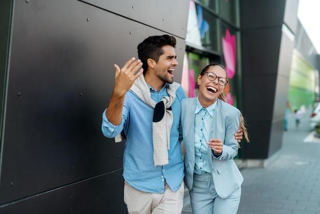 Glückliches multikulturelles paar, das umarmt, lächelt und spricht, während es auf der straße geht