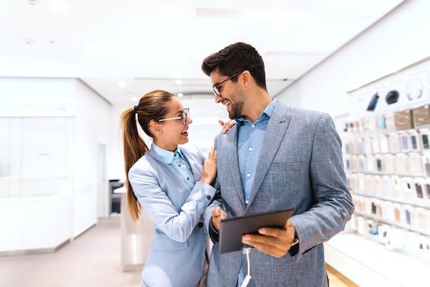 Glückliches multikulturelles paar in der formellen abnutzung, die neues tablet kauft, während es im tech-laden steht. mann hält tablette, während frau sich auf ihn stützt.