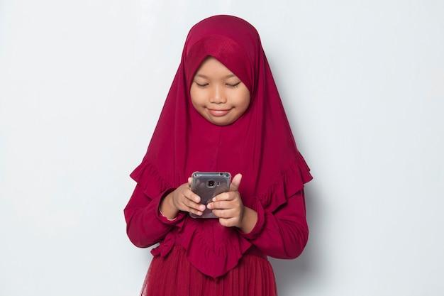 Glückliches muslimisches asiatisches kleines mädchen mit smartphone auf weißem hintergrund