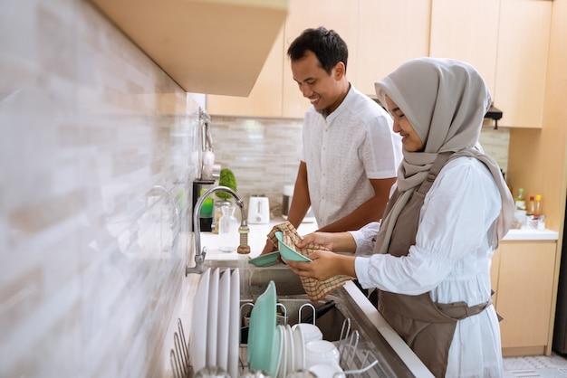 Glückliches muslimisches junges paar spült das geschirr, nachdem es zusammen iftar abendessen in der küchenspüle gegessen hat