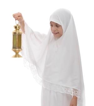 Glückliches muslimisches mädchen, das mit festlicher ramadan-laterne feiert