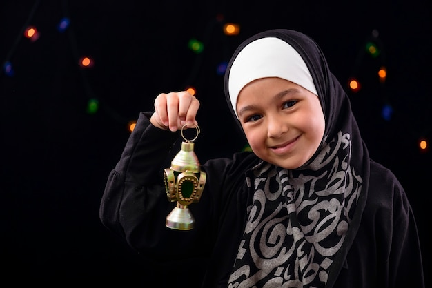 Glückliches muslimisches mädchen, das mit ramadan-laterne feiert
