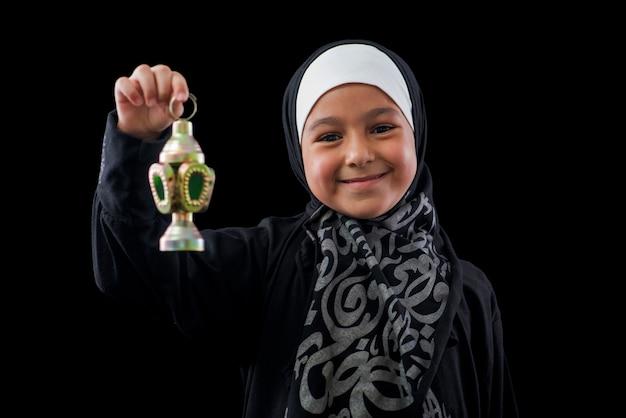 Glückliches muslimisches mädchen, das mit ramadan-laterne über schwarzem hintergrund lächelt