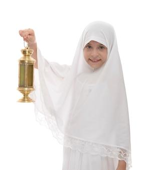 Glückliches muslimisches mädchen, das ramadan feiert, der festliche laterne hält