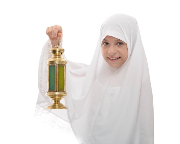 Glückliches muslimisches mädchen, das ramadan laterne hält