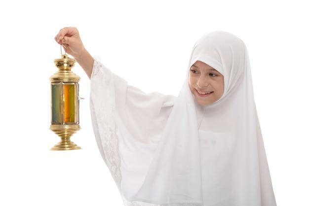 Glückliches muslimisches mädchen, das ramadan mit festlicher laterne feiert
