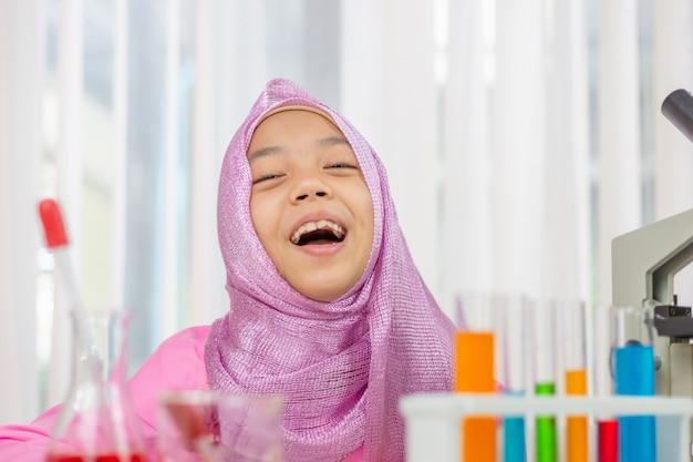 Glückliches muslimisches mädchen, das wissenschaft studiert