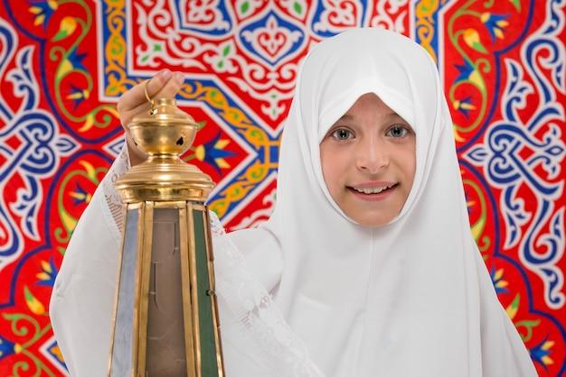 Glückliches muslimisches mädchen mit festlicher ramadan-laterne