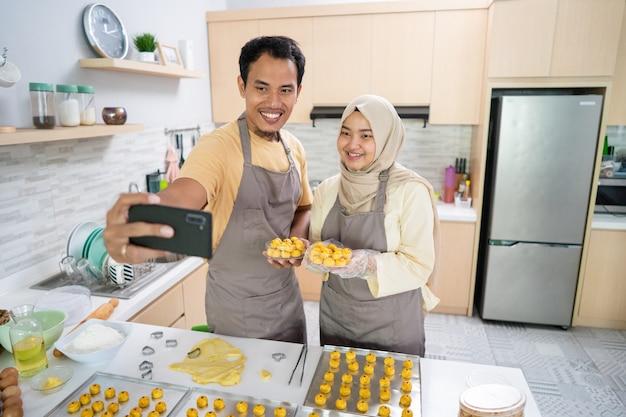 Glückliches muslimisches paar, das selfie mit ihrem essen macht, das zu hause zusammen in der küche gemacht wird. eid mubarak feier kochen