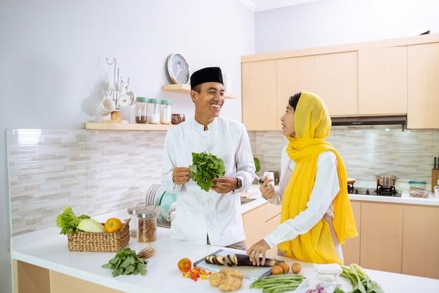 Glückliches muslimisches paar, das zusammen in der küche kocht. mann und frau bereiten sich auf das abendessen vor