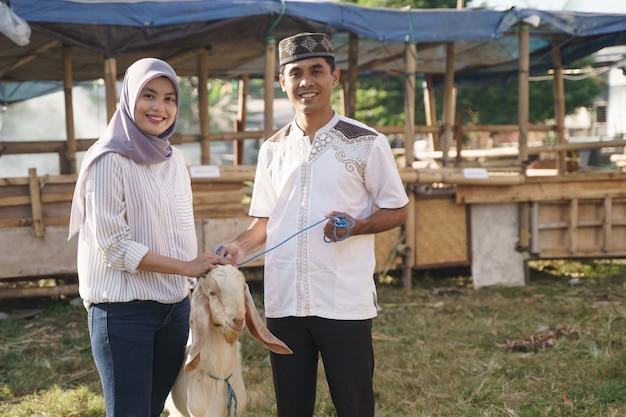 Glückliches muslimisches paar kauft eine ziege für eid adha opfer oder korbanfeier