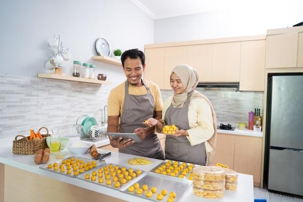 Glückliches muslimisches paar mit tabletten-pc, der einen nastar-kuchen backt