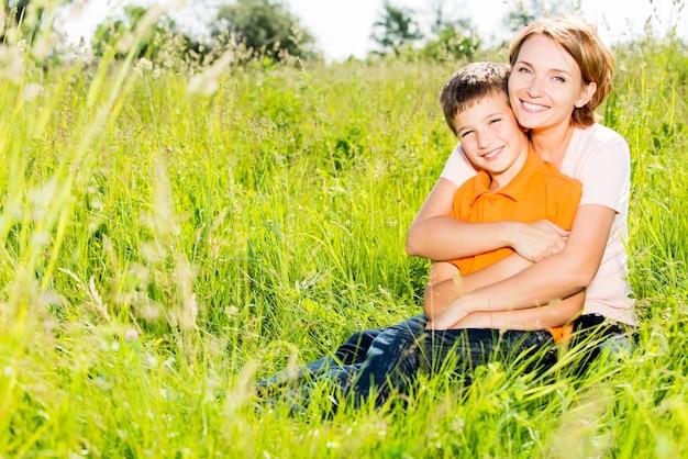 Glückliches mutter- und sohn im außenporträt der frühlingswiese