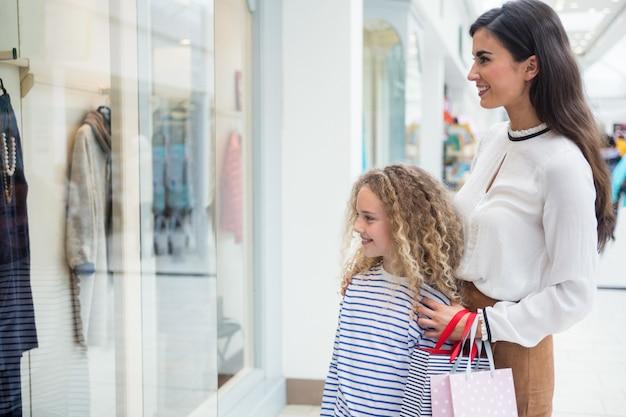 Glückliches mutter- und tochterfenstereinkaufen im mall