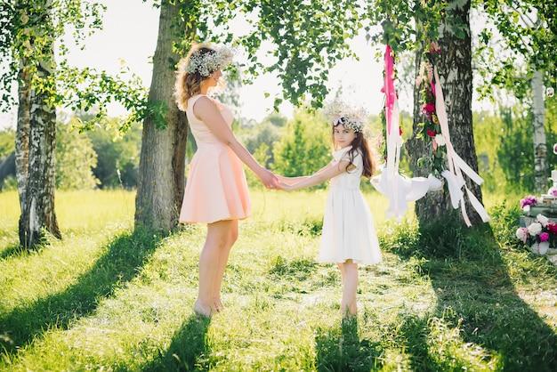 Glückliches mutter- und tochterhändchenhalten im sommer