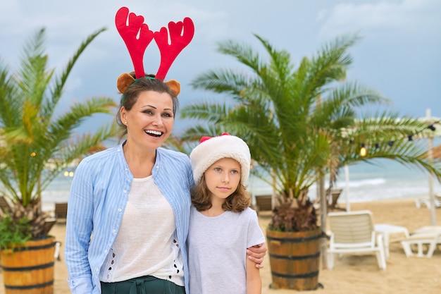 Glückliches mutter- und tochterkind in der weihnachtsmannmütze, die spaß hat, entlang strandhändchen haltend zu gehen