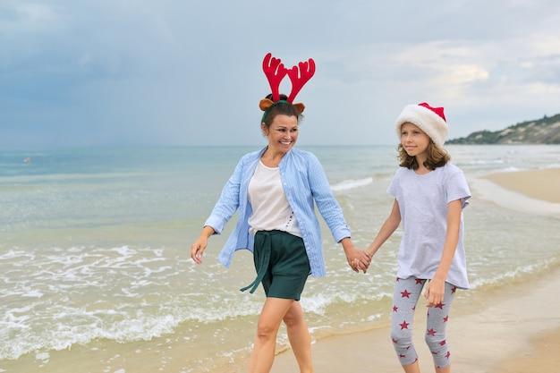 Glückliches mutter- und tochterkind in der weihnachtsmütze, die händchenhalten entlang des strandes geht
