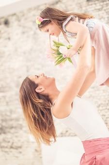 Glückliches muttertagskonzept. mama nimmt ihr kind vor freude über den kopf.