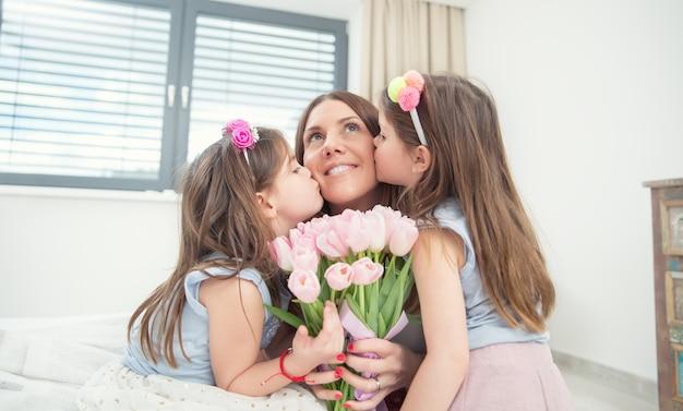 Glückliches muttertagskonzept. zwillinge der kleinen töchter küssen ihre mutter mit einem tulpenstrauß.