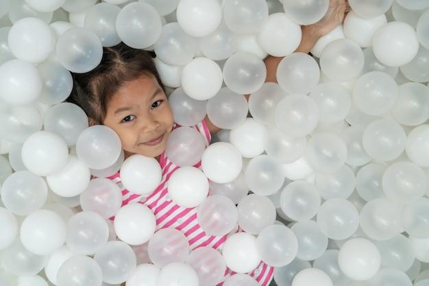 Glückliches nettes asiatisches kindermädchen, das spaß hat, mit weißen plastikbällen im spielplatz zu spielen